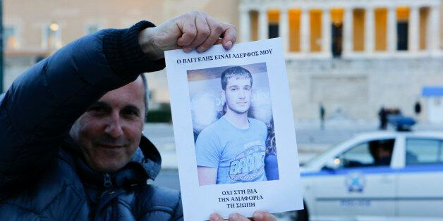 SYNTAGMA SQUARE, ATHENS, ATTICA, GREECE - 2015/03/16: A man holds up a poster with a picture of Vangelis...