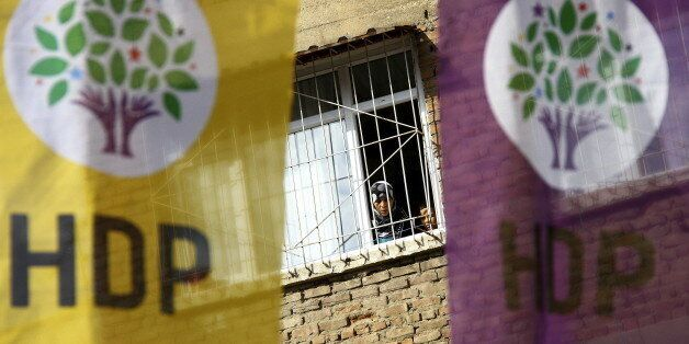 A woman and a boy look out of a balcony as election banners of the pro-Kurdish Peoples' Democratic Party...