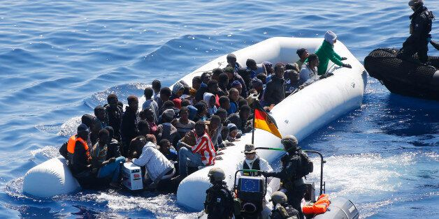 In this March 29, 2016 picture German Navy sailors ad Finish Special Forces surround a boat with migrants...