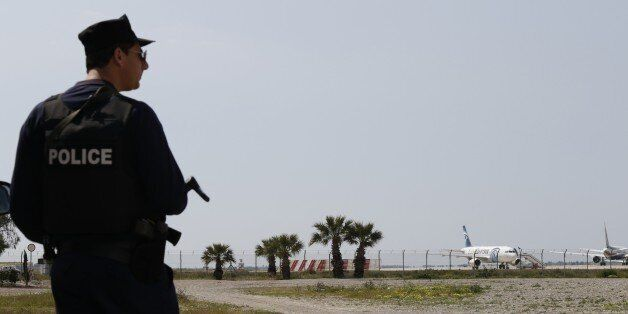 A Cypriot policeman stands guard in the vicinity of Larnaca airport where an EgyptAir Airbus A-320 (R)...