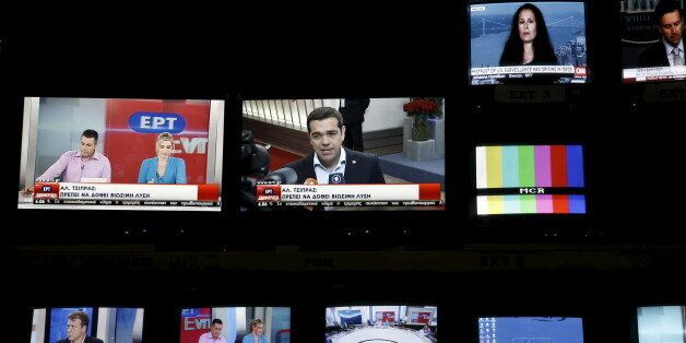 Greek Prime Minister Alexis Tsipras is seen on a monitor screen (C) at the control room during the first...