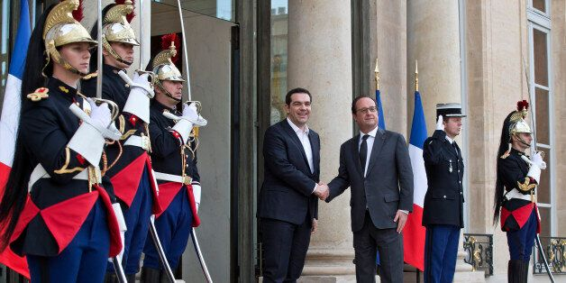 Greek Prime Minister Alexis Tsipras, left, is welcomed by French President Francois Hollande at the Elysee...