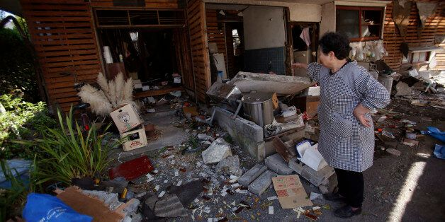 A local resident cleans up her house in Mashiki, Kumamoto prefecture, southern Japan, Friday, April 15,...