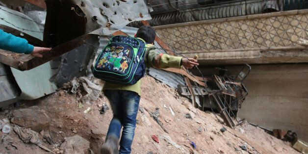 A child navigates through rubble and barbed wire in Aleppo, Syria, Thursday, Feb. 11, 2016. Fighting...