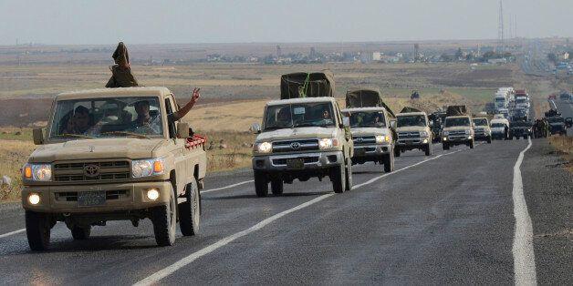 A convoy of peshmerga vehicles makes its way to the Turkish-Syrian border, near the town of Kiziltepe,...