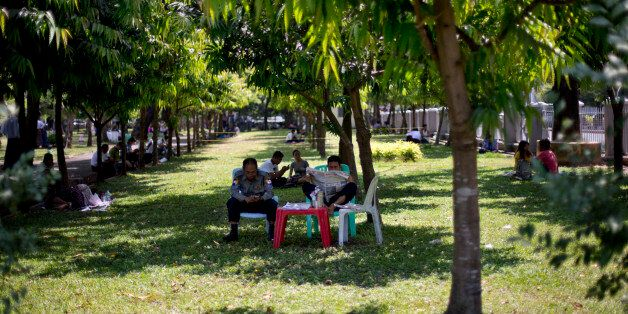 Police officers sit in the shade of a tree in a hot humid day at a public park in Yangon, Myanmar, Thursday,...