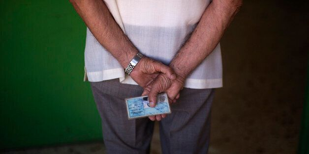 A man holds his ID card as he waits for his turn to cast his vote at a polling station in Athens, Sunday,...