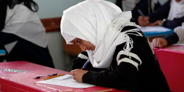 A Yemeni female student sits for the mid-year school exams at a secondary school on February 9, 2016...