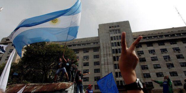 Supporters of former Argentine President Cristina Fernandez de Kirchner wave an Argentine national flag...