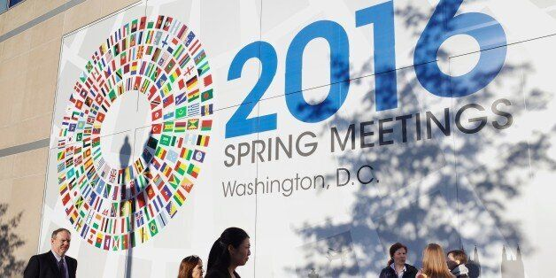 People are seen in front of a banner during the 2016 International Monetary Fund, World Bank Spring Meetings...