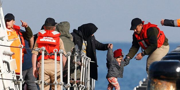 Migrants disembark from a Turkish coastguard boat after a failed attempt at crossing to the Greek island...