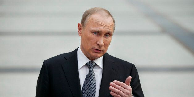 Russian President Vladimir Putin gestures speaking to the media after his marathon call-in TV show in...