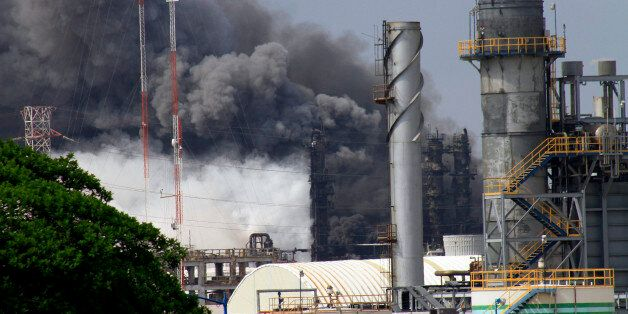 Military personnel take care of the first injured workers after an explosion at the Pajaritos PEMEX petrochemical...