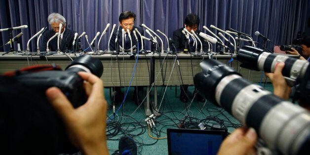 Mitsubishi Motors President Tetsuro Aikawa, center, listens to a reporter's question during a press conference...