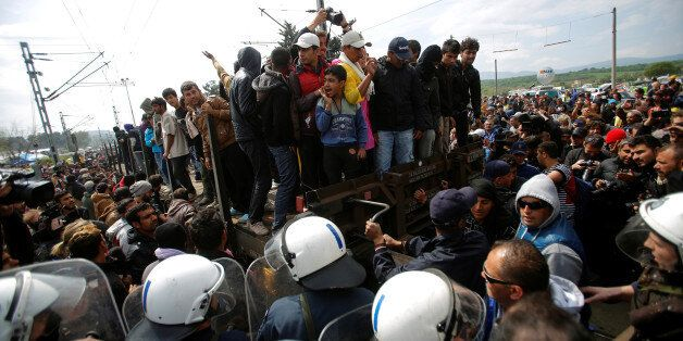 Migrants and refugees are stopped by Greek police after trying to push a train carriage through a police...
