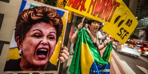 SAO PAULO, BRAZIL - APRIL 14: A woman holds a banner during a protest against the government of president...