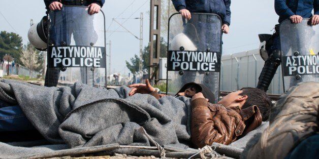 EIDOMENI, GREECE - 2016/03/22: Refugee kids sleeping on the railway lines in front of police forces as...