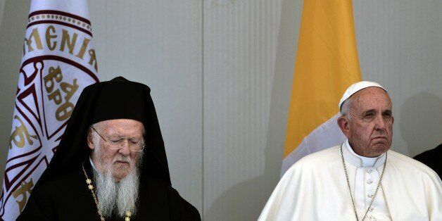 Patriarch Bartholomew (L) sits next to Pope Francis during their visit at the Moria detention center...