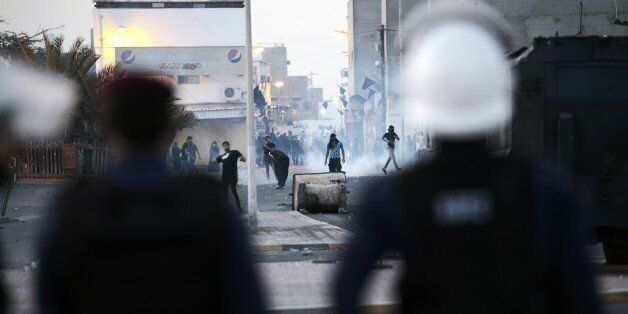 Bahraini protestors throw stones towards riot police during clashes following the funeral of Ali Abdulghani,...