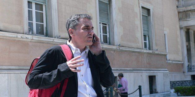 Greek Finance Minister Euclid Tsakalotos talks on his mobile phone outside the Greek parliament in Athens...