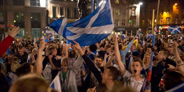 Supporters of the Yes campaign in the Scottish independence referendum cheer with Scottish Saltire flags...