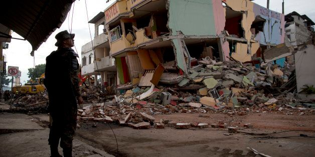 An air force soldier stands guard in front of buildings collapsed by an earthquake in Manta, Ecuador,...