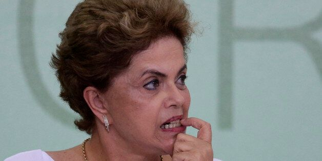Brazil's President Dilma Rousseff bites on her fingernail during a signing ceremony for land reform agreements,...