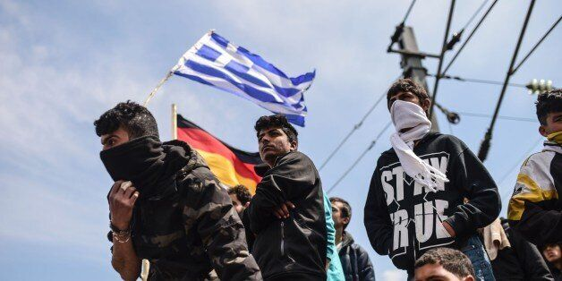Refugees and migrants hold German and Greece flags as they protest to reopen the border near their makeshift...