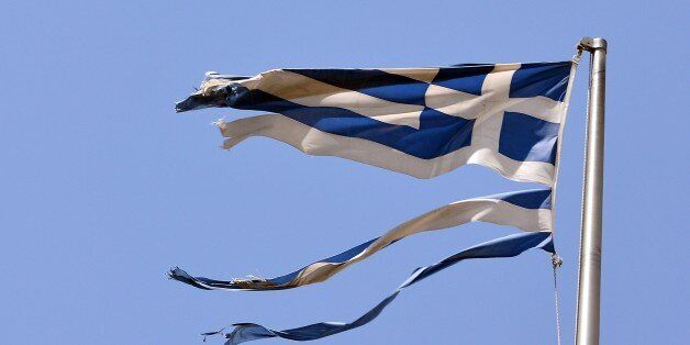 A ripped off Greek national flag flutters in central Athens on July 22, 2015. Prime Minister Alexis Tsipras...