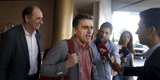 Greek Finance Minister Euclid Tsakalotos (C) speaks to the media while Economy Minister George Stathakis...