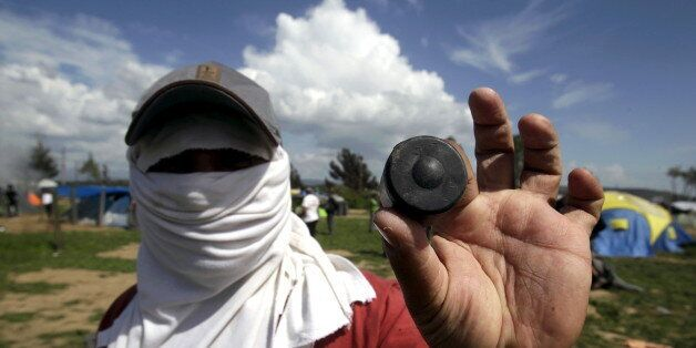 A protesting migrant displays a rubber bullet he says was fired by Macedonian police during clashes at...