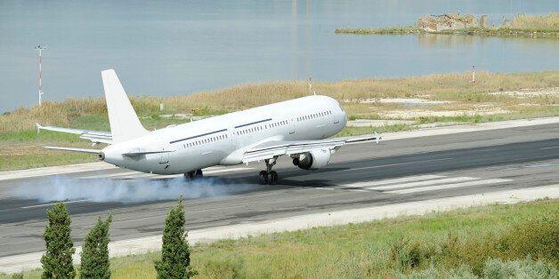 Passenger airplane landing to runway, city of Kerkira, Corfu island,