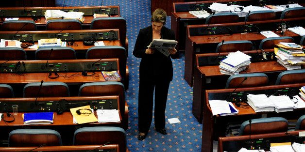 A Macedonian member of parliament reads a newspaper during a parliament session in Skopje early April...