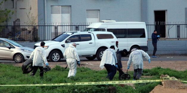 Forensic officials work at explosion site, after several police officers were killed in an explosion...