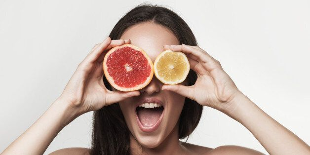 Funny portrait of young brunette woman holding fresh lemon and grapefruit. Healthy eating lifestyle and...