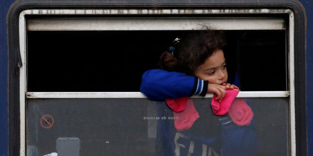 A migrant girl looks from inside a rail car at a train station near a make shift refugee camp at the...