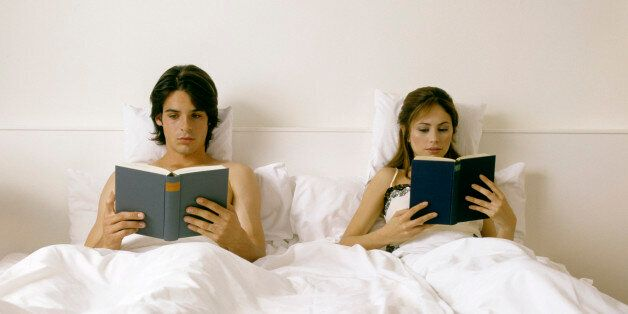 couple lying in bed, reading books