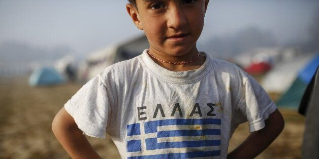 A child wearing a t-shirt with Greek flag stands at a makeshift camp for migrants and refugees at the...