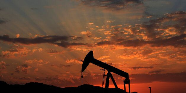 FILE - In this Dec. 13, 2015 file photo the sun sets behind an oil pump in the desert oil fields of Sakhir,...