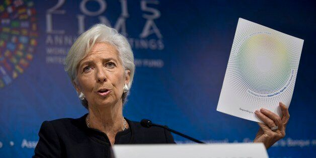 International Monetary Fund chief Christine Lagarde holds up a folder labeled Global Policy Agenda during...