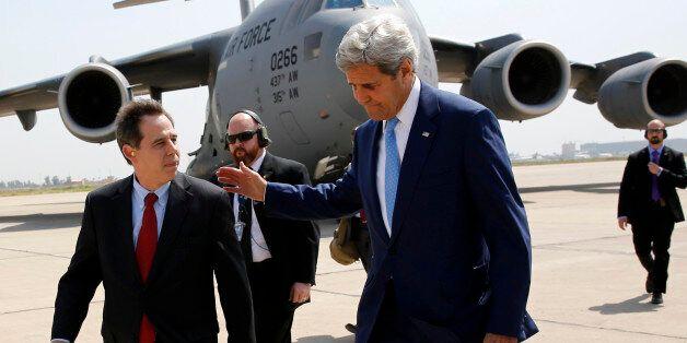 US ambassador to Iraq Stuart Jones (L) walks with Secretary of State John Kerry (R) as he arrives via...