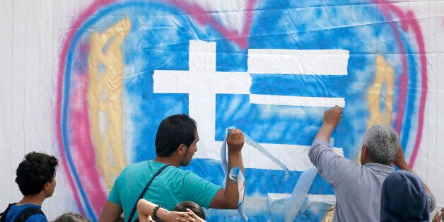 Migrants paint a graffiti at the tent in the makeshift refugee camp at the northern Greek border point...