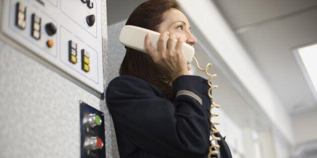 Stewardess instructing passengers on airplane over the