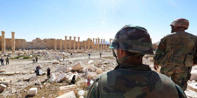 In this picture taken Friday, April 1, 2016, soldiers look over damage at the historical Bel Temple in...