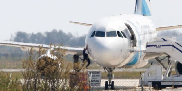TOPSHOT - A man climbs out of the cockpit window an EgyptAir Airbus A-320 parked at the tarmac of Larnaca...