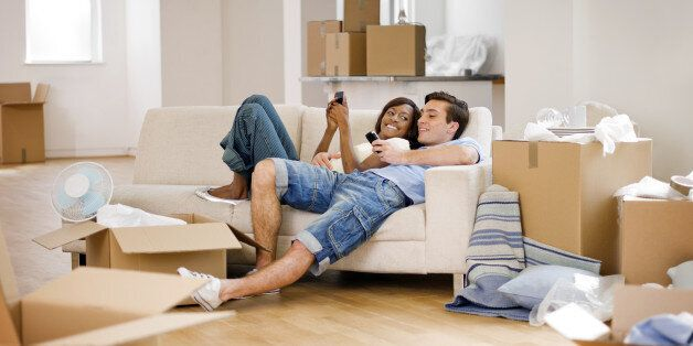 A young couple relaxing on a sofa and texting after moving into a