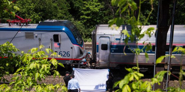 WASHINGTON, DC - MAY 14: An Amtrak train slowly crawls by officers as they hold up a sheet covering remains...