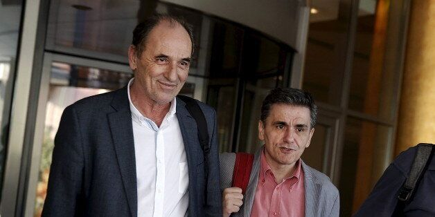 Greek Economy Minister George Stathakis (L) and Finance Minister Euclid Tsakalotos leave a hotel following...