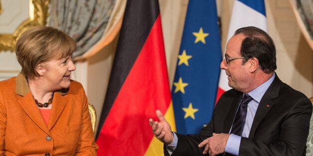 French president Francois Hollande, right, speaks to German Chancellor Angela Merkel during their meeting...