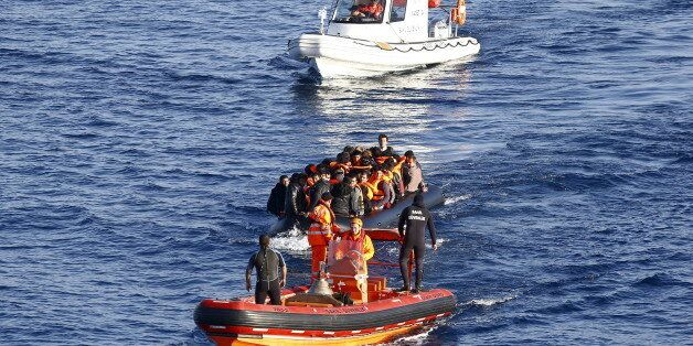 A Turkish Coast Guard fast rigid-hulled inflatable boat tows a dinghy filled with refugees and migrants...